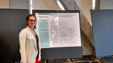 undergraduate student researcher with poster presentation